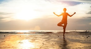 Jonge vrouw het praktizeren yoga op het strand bij zonsondergang meditatie Royalty-vrije Stock Foto's