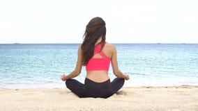 Jonge vrouw het praktizeren yoga op het strand bij zonsondergang Oefeningenkalmte en harmonie De meditatie in lotusbloem stelt Ge stock footage