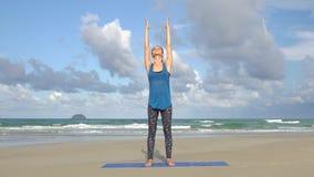 Jonge vrouw het praktizeren yoga op het strand voor overzees Gezond Actief Levensstijlconcept stock videobeelden