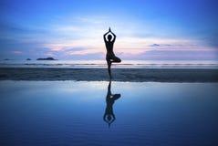 Jonge vrouw het praktizeren yoga op strand bij surrealistische zonsondergang