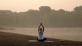 Jonge vrouw het praktizeren yoga op het strand bij zonsondergang stock videobeelden