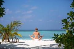 Jonge vrouw het praktizeren yogameditatie op het strand die de oceaan onder ogen zien dichtbij een palm op de Maldiven Royalty-vrije Stock Foto