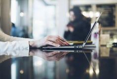 Jonge vrouw het schrijven teksthanden op open laptop in een koffie op een lijst die met bezinning en glans, onderneemster aan com royalty-vrije stock fotografie
