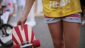 Jonge vrouw in het skateboard van de borrelsdraai met rode wielen in handen De avond van de zomer Heldere spijkers stock video