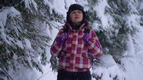 Jonge vrouw in het sneeuwhout Jonge mooie toeristentribunes alleen in het bos en de blikken rond E stock video
