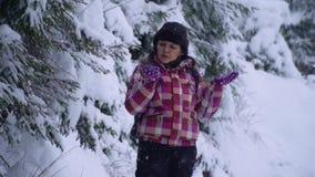 Jonge vrouw in het sneeuwhout Jonge mooie toeristentribunes alleen in het bos en de blikken rond E stock videobeelden