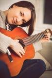 Jonge vrouw het spelen gitaar thuis Ontspannen gelukkige jonge vrouw met het portret van het muziekinstrument royalty-vrije stock foto's