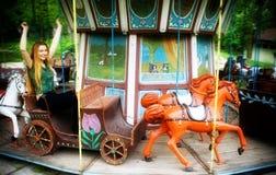 Jonge vrouw in het spinnen van carrousel Stock Fotografie
