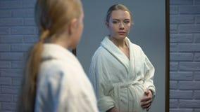 Jonge vrouw het strijken buik die spiegelbezinning, die vrouwelijke tiener verwachten kijken stock videobeelden