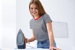 Jonge vrouw het strijken kleren aan boord stock foto's