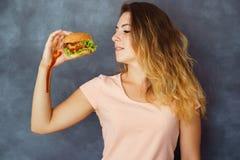 Jonge vrouw het vechten verleiding om hamburger te eten royalty-vrije stock afbeeldingen