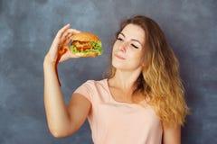 Jonge vrouw het vechten verleiding om hamburger te eten stock afbeeldingen