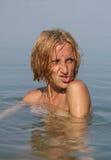 Jonge vrouw in het water die een gezicht maken Stock Foto