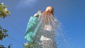 Jonge vrouw het water geven installaties met gieter stock videobeelden