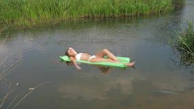 Jonge Vrouw in het Witte Zwempak het Zonnebaden Leggen op Matras in het Water stock videobeelden