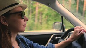 Jonge vrouw in hoed en zonnebril die een auto drijven stock footage