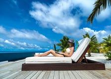 Jonge vrouw in hoed met laptop bij het strand Royalty-vrije Stock Afbeelding