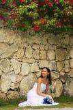 Jonge vrouw in huwelijkskleding het stellen voor de steenmuur w royalty-vrije stock afbeelding