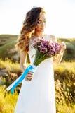 Jonge vrouw in huwelijkskleding in openlucht Mooie bruid op een gebied bij zonsondergang Stock Fotografie