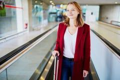 Jonge vrouw in internationale luchthaven met bagage royalty-vrije stock afbeelding