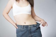 Jonge vrouw in jeans van grote grootte, concept gewichtsverlies stock foto's