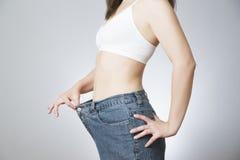 Jonge vrouw in jeans van grote grootte, concept gewichtsverlies royalty-vrije stock afbeeldingen