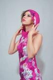 Jonge vrouw in karmozijnrode kleding op grijze achtergrond Stock Foto
