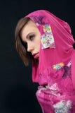 Jonge vrouw in karmozijnrode kleding op zwarte achtergrond Royalty-vrije Stock Foto