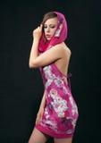 Jonge vrouw in karmozijnrode kleding op zwarte achtergrond Stock Foto's