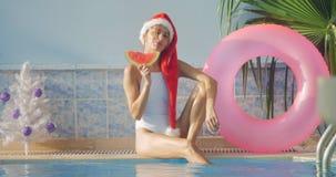 Jonge vrouw in Kerstmishoed in zwempak, nieuw jaarthema stock videobeelden