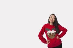 Jonge vrouw in Kerstmissweater die zich met handen op heupen over grijze achtergrond bevinden royalty-vrije stock foto's