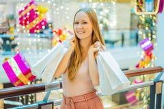 Jonge vrouw in Kerstmiswandelgalerij met Kerstmis het winkelen Schoonheidsbu stock foto's
