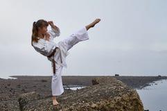 Jonge vrouw in kimono het praktizeren karate royalty-vrije stock foto