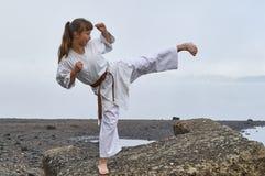 Jonge Vrouw in Kimono het praktizeren karate op rivierkust stock foto's