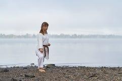 Jonge Vrouw in Kimono het praktizeren karate op rivierkust royalty-vrije stock fotografie
