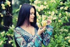 Jonge vrouw in kleding het ontspannen in tuin Royalty-vrije Stock Afbeeldingen