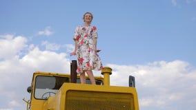 Jonge vrouw in kledings golvende hand en het springen op kap van tractor op achtergrondhemel met witte wolken stock video