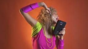 Jonge vrouw in kleurrijke retro kleren die met een oude cassette dansen stock videobeelden
