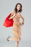 Jonge vrouw in kleurrijke uitrusting, die een zak houdt Stock Afbeeldingen