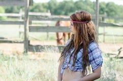 Jonge vrouw in landbouwbedrijf met krullend haar stock foto