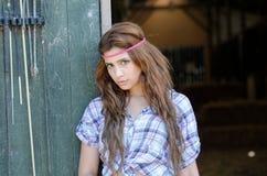 Jonge vrouw in landbouwbedrijf met plaidoverhemd, die tegen de deur leunen stock afbeelding