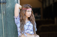 Jonge vrouw in landbouwbedrijf met plaidoverhemd, die tegen de deur leunen royalty-vrije stock fotografie