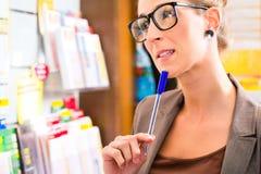 Jonge vrouw in Lottowinkel het spelen kaartje Stock Foto
