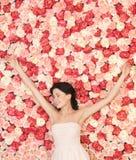 Jonge vrouw met achtergrondhoogtepunt van rozen stock fotografie