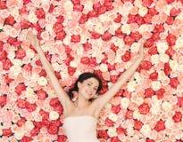 Jonge vrouw met achtergrondhoogtepunt van rozen royalty-vrije stock foto's