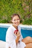 Jonge vrouw met appel bij pool royalty-vrije stock afbeeldingen