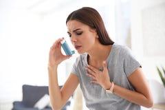 Jonge vrouw met astmainhaleertoestel stock afbeeldingen