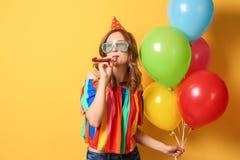 Jonge vrouw met ballons en partijventilator op kleurenachtergrond Verjaardagsviering stock foto's