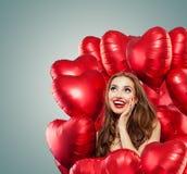 Jonge vrouw met ballons rood hart Verrast meisje die met rode lippenmake-up, krullend haar en leuke glimlach omhoog kijken royalty-vrije stock afbeelding
