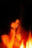 Jonge Vrouw met Basgitaar en Vlammen royalty-vrije stock afbeelding